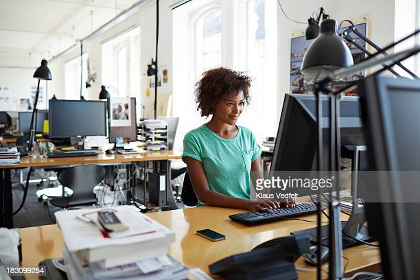 woman typing on computer at her desk - leanincollection stock pictures, royalty-free photos & images