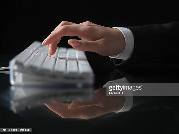 Woman typing on computer keyboard, close-up of hand