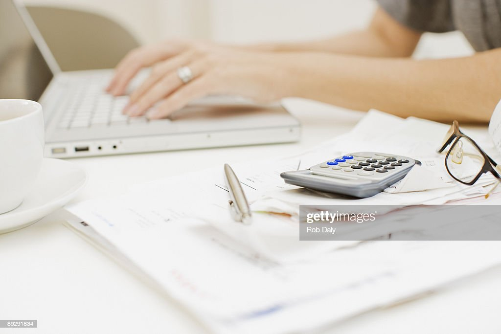 Woman typing on laptop near bills and calculator : Stock Photo