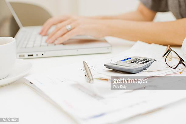 Mujer escribiendo en computadora portátil, cerca de las facturas y calculadora