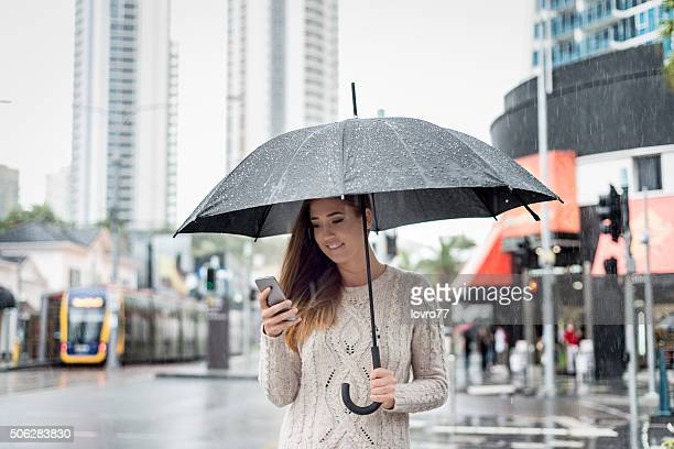 Woman typing text message in rainy day