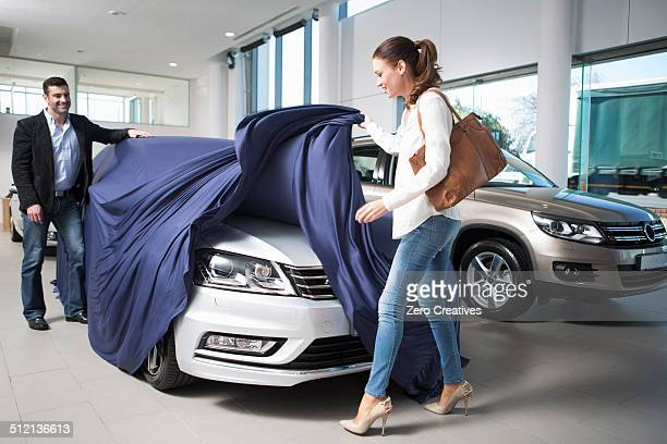 Woman uncovering new car with boyfriend in car dealership