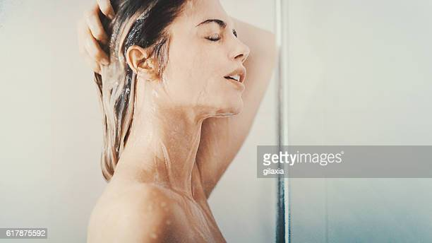 woman under a relaxing shower. - shampoo stock-fotos und bilder