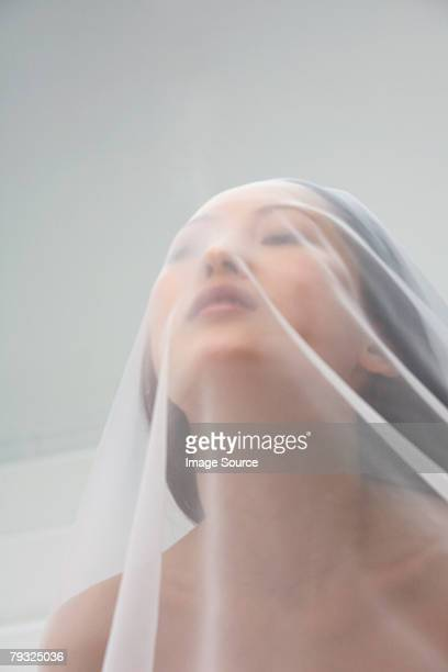 Woman under a translucent sheet