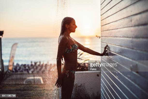 Woman under beach shower