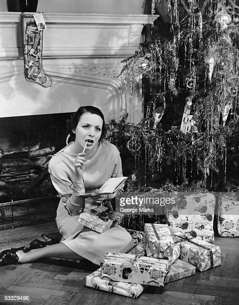 Woman under Christmas tree making list