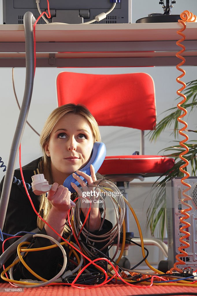 woman under desk on phone with wires : Stock Photo