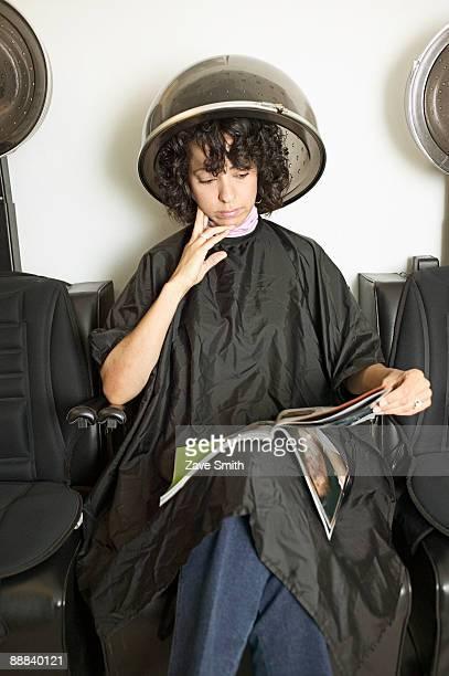 Woman under hair dryer reading a magazine