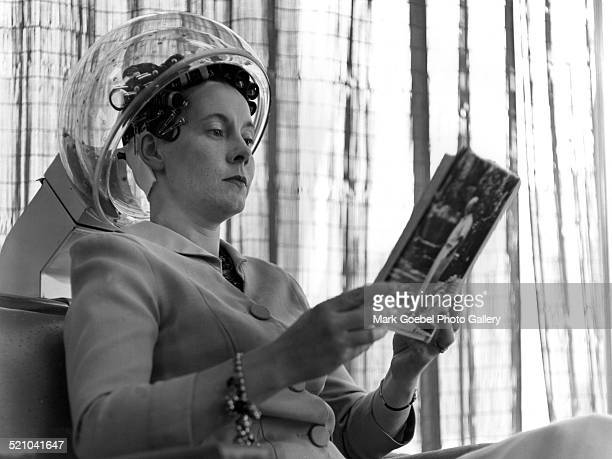 Woman under hairdryer reading magazine in beauty salon late 1950s or early 1960s