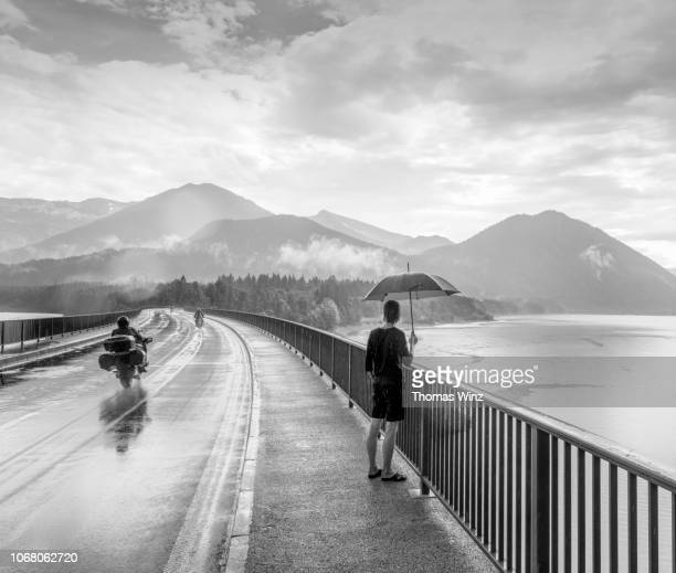 woman under red umbrella - women black and white motorcycle stock pictures, royalty-free photos & images