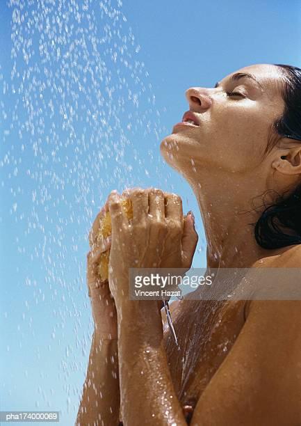 Woman under shower, hands under head holding sponge, side view, close-up