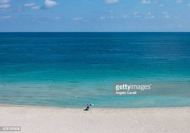Woman under sun umbrella on deserted beach