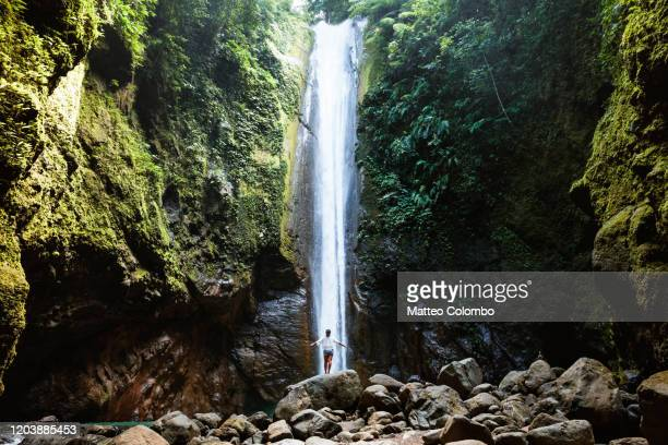 woman under tall waterfall, negros, philippines - filipino ethnicity and female not male fotografías e imágenes de stock