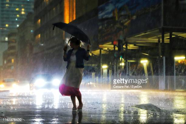 woman under umbrella standing on street during rainfall - sydney rain stock pictures, royalty-free photos & images
