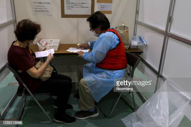 Woman undergoes a health check prior to receiving a dose of the Pfizer-BioNTech Covid-19 vaccine at an inoculation site at Miyakojima Sports Center...