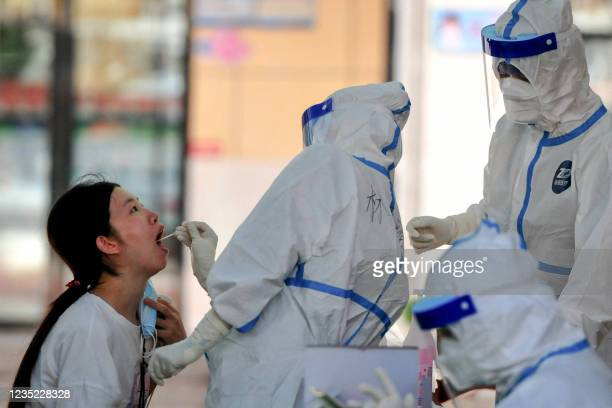 Woman undergoes a nucleic acid test for the Covid-19 coronavirus in Xianyou county, Putian city, in China's eastern Fujian province on September 13,...
