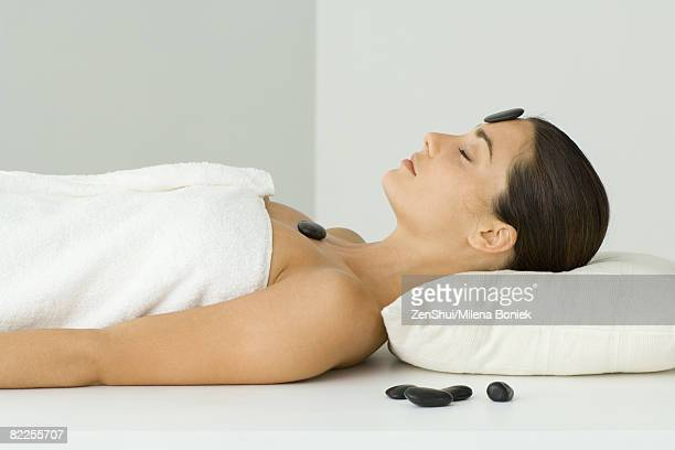 Woman undergoing lastone therapy, eyes closed