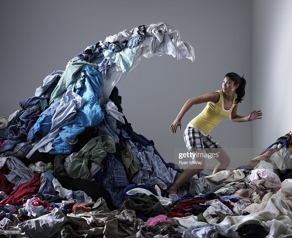 Woman underneath wave of laundry : Stock Photo