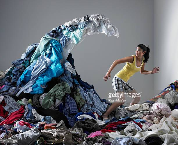 woman underneath wave of laundry - heap stock pictures, royalty-free photos & images