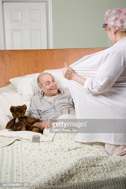 woman undressing in front of man in bed - 69 position stock photos and pictures