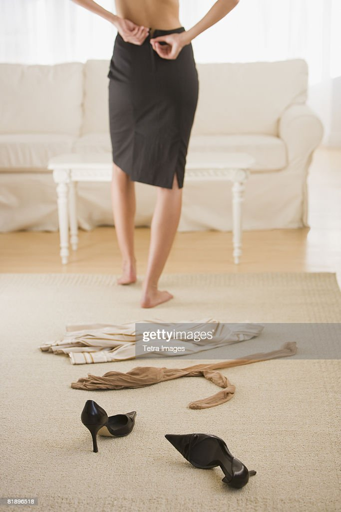 Woman undressing next to clothing on floor : Stock Photo