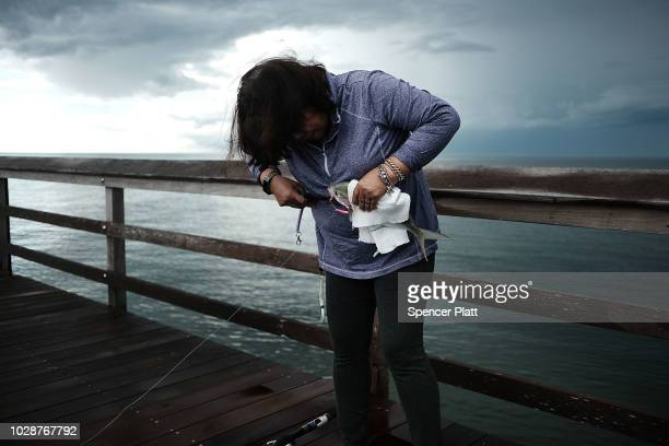 A woman unhooks a fish along the Naples Pier on September 7 2018 in Naples Florida Despite being largely clear of the red tide that has plagued the...