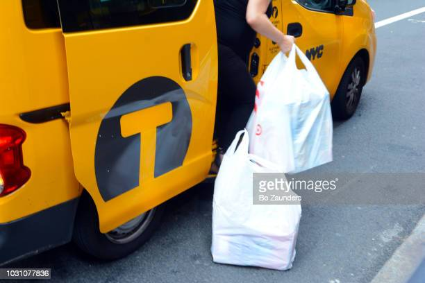 Woman unloading bags from a cab in New York City.