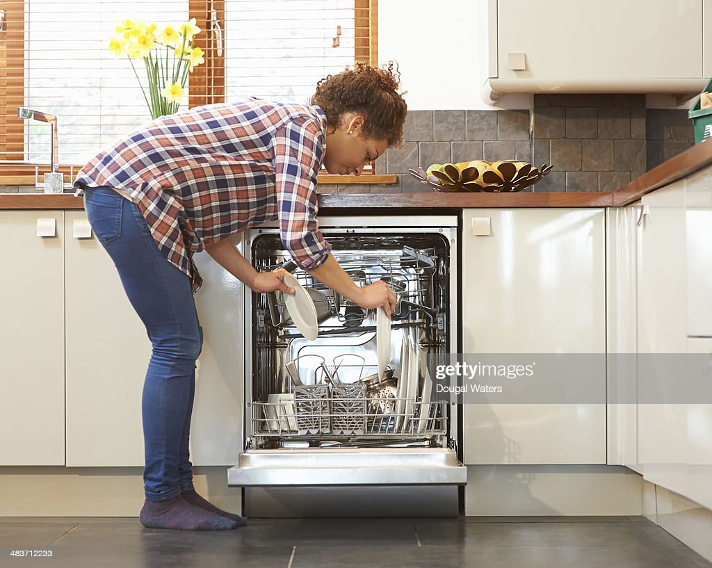 Woman unloading dish washer in kitchen. : Stock Photo