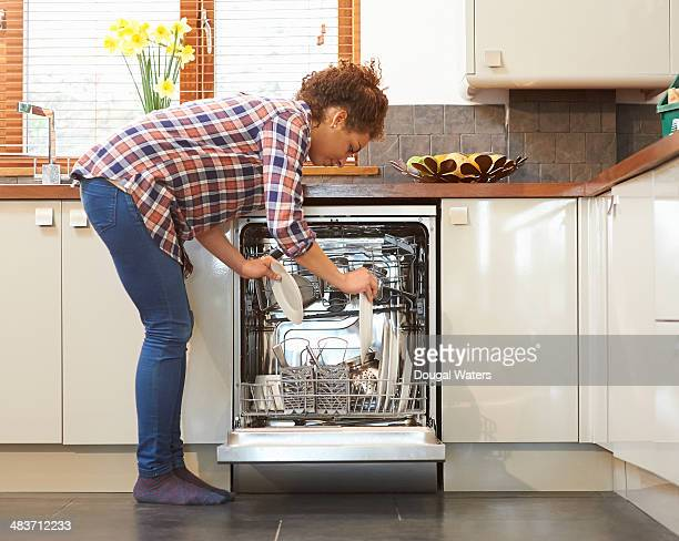 woman unloading dish washer in kitchen. - bending stock pictures, royalty-free photos & images