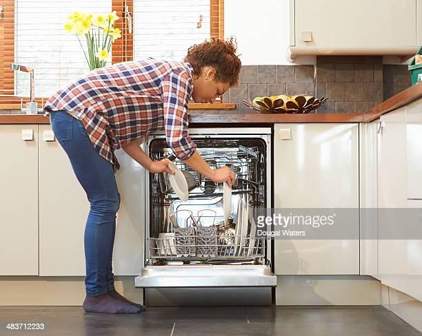 woman unloading dish washer in kitchen. - beugen oder biegen stock-fotos und bilder
