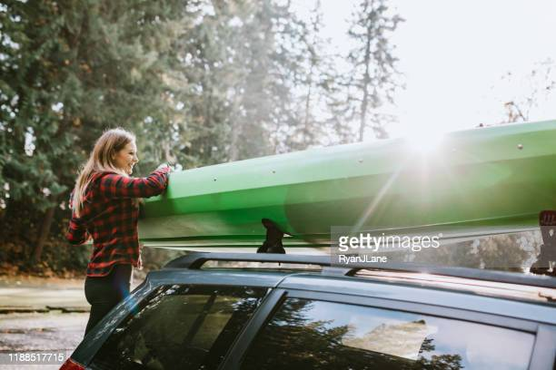 woman unloading kayak from car on pacific northwest adventure - kayak stock pictures, royalty-free photos & images