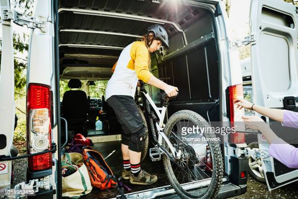 Woman unloading mountain bike from back of van before ride