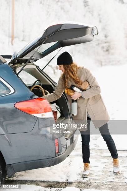 A woman unloading the shopping from the boot of a car.