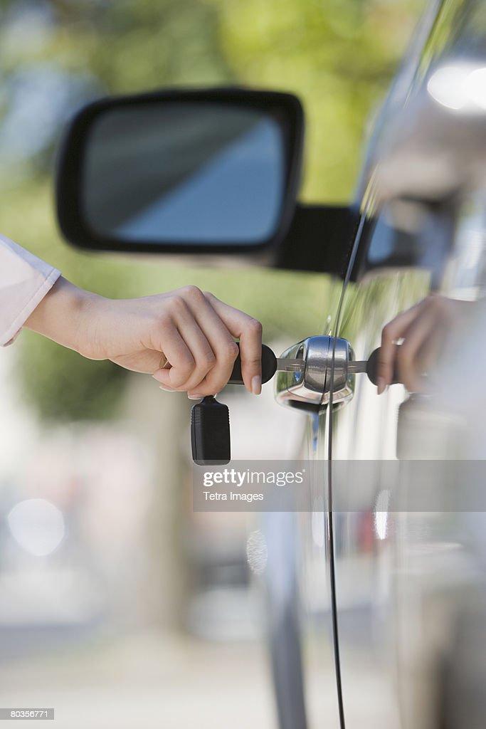 Woman unlocking car door : Stock Photo