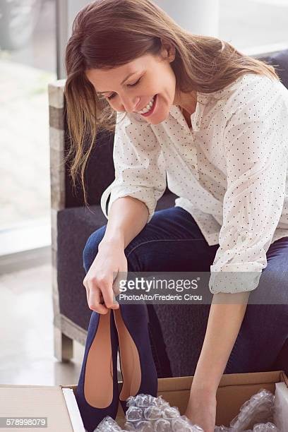 Woman unpacking box of new shoes