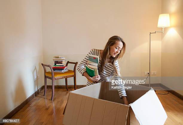 woman unpacking box with books in her new house