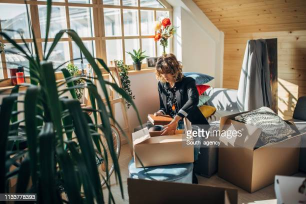 woman unpacking boxes in new home - one young woman only stock pictures, royalty-free photos & images