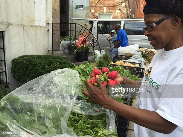 A woman unpacking fresh radishes and other fresh produce placed on tables at a church sponsored community food drive outdoors on the sidewalk to be...