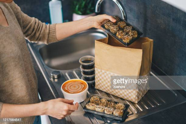 woman unpacking takeaway food delivery - box container stock pictures, royalty-free photos & images