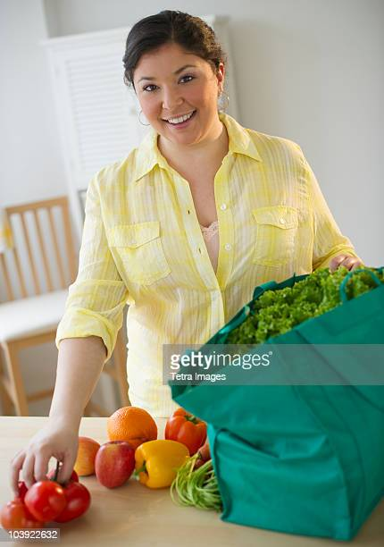 Woman unpacking vegetables from grocery bag