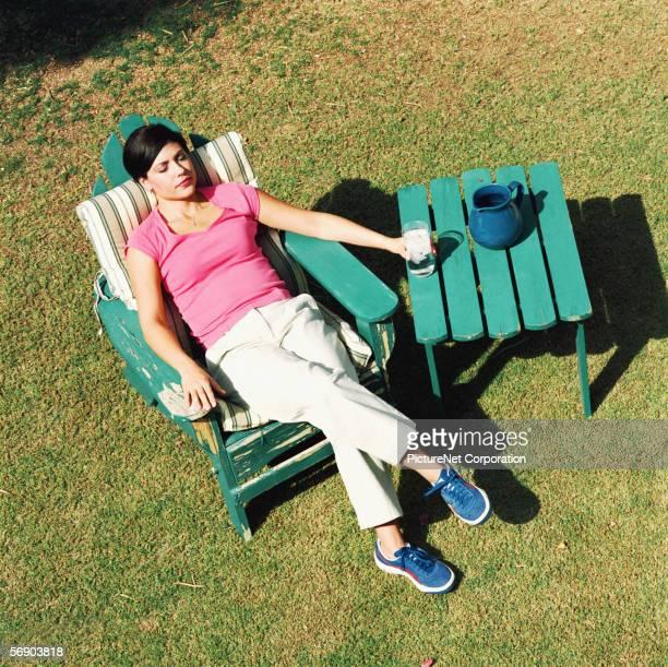 Woman unwinding in yard with iced drink