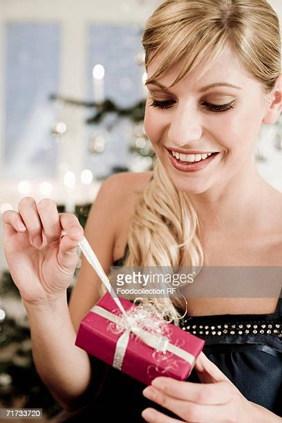 Woman unwrapping Christmas gift