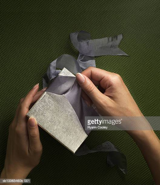 Woman unwrapping gift, close-up of hands
