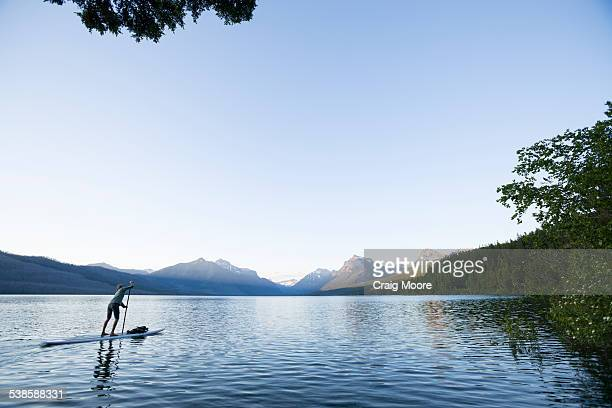 A woman up paddle boards (SUP) on Lake McDonald in Glacier National Park.