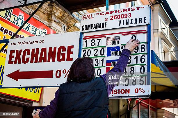 Woman updates the Exchange rate between the US-Dollar and Moldovan Lei on a billboard on March 9, 2015 in Chisinau, Moldova. The Republic of Moldova...