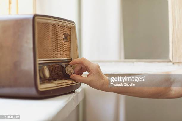 woman use an old traditional radio - radio antigua fotografías e imágenes de stock