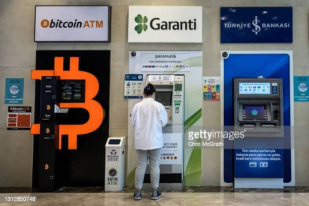 Woman uses a bank ATM next to a Bitcoin ATM machine at a shopping mall on April 16, 2021 in Istanbul, Turkey. Turkey's Central Bank announced a ban...