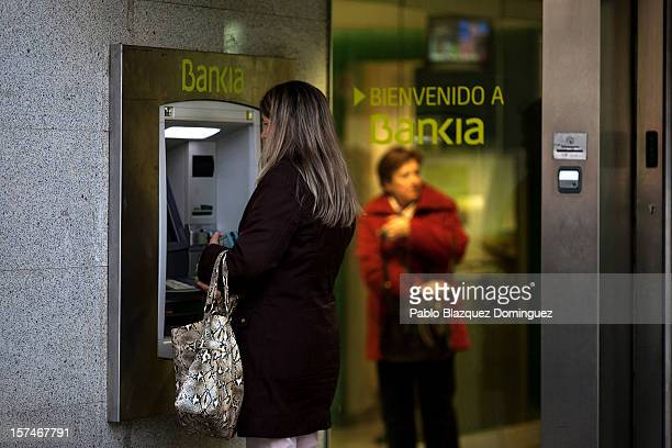 A woman uses a Bankia's cash point at Plaza de Castilla on December 3 2012 in Madrid Spain Spain has formally requested 395 euro billions bank...