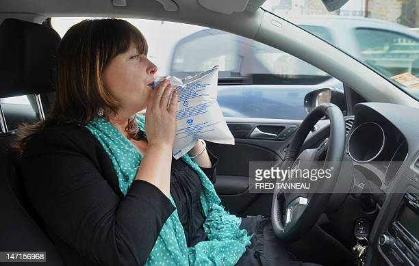 A woman uses a breathalyser on June 26 2012 in the French western city of Quimper In France from July 1 each motor vehicle of more than 50 cm3 must...