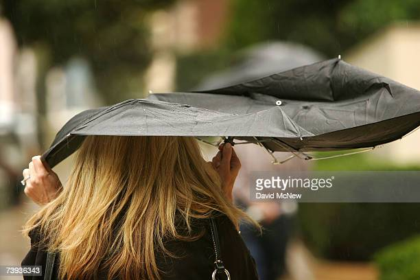 A woman uses a broken umbrella downtown as a lateseason Pacific storm brings rain and snow to southern California April 20 2007 in Los Angeles...